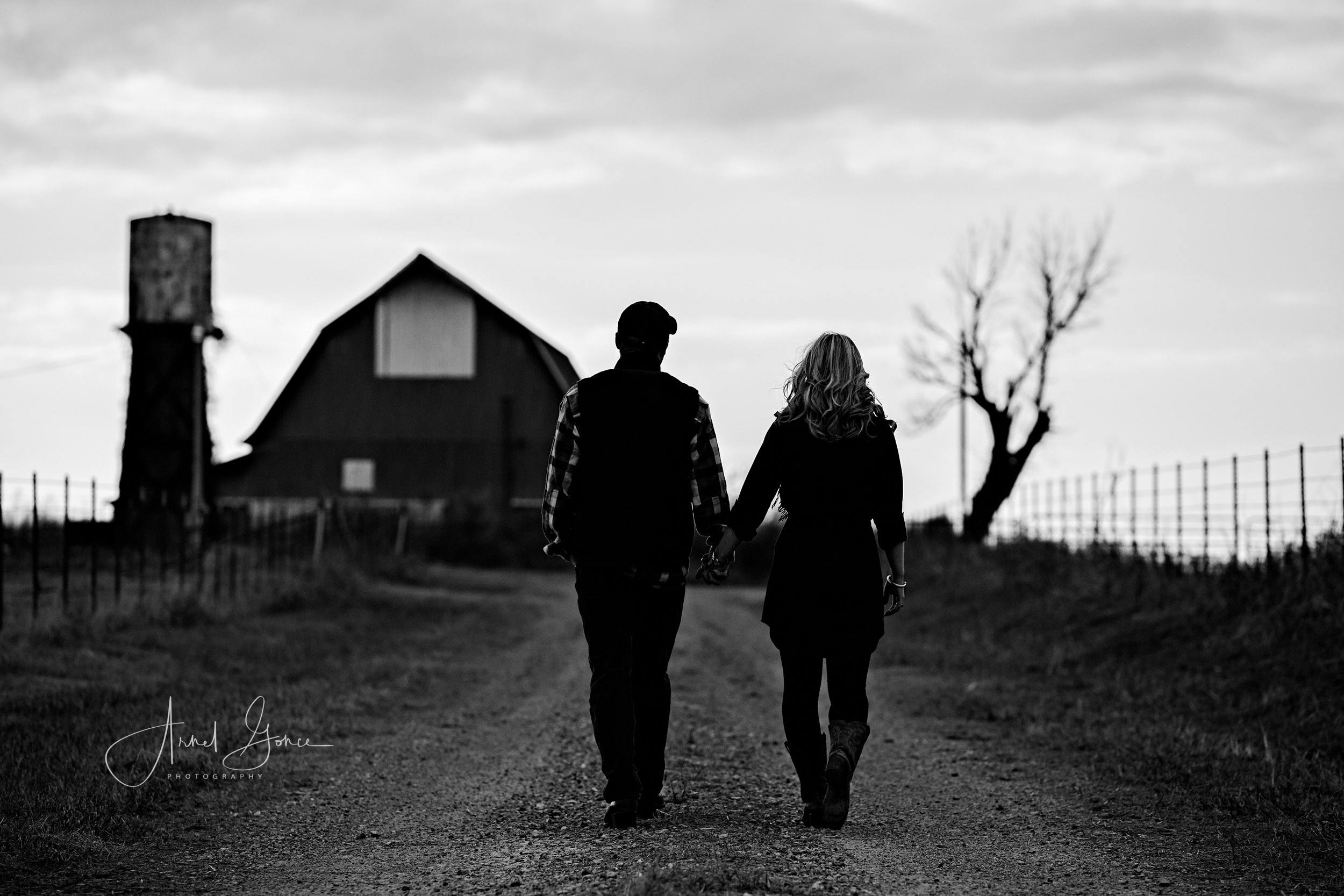 Engaged couple walking hand in hand toward the barn in the black and white image of an engagement photography session.
