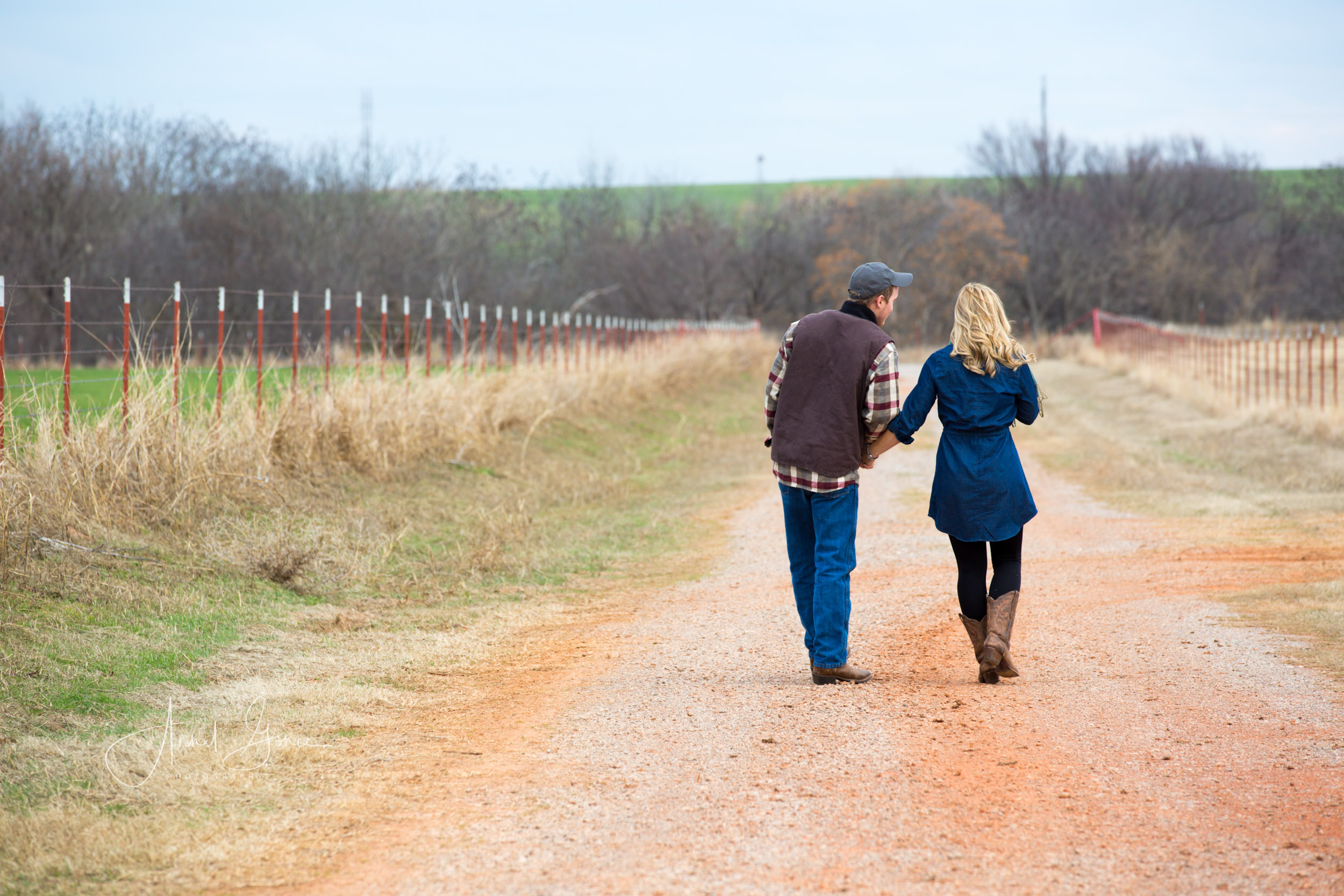 Couple walking hand in hand down the driveway of a farm in Piedmont Ok, west of Edmond.
