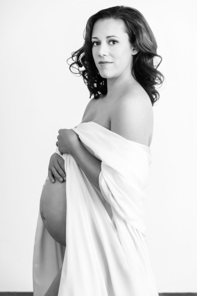 White heavy silk sheeting as a wrap for 8 month pregnant mom during her maternity portraits.  Black and white image against a white background.