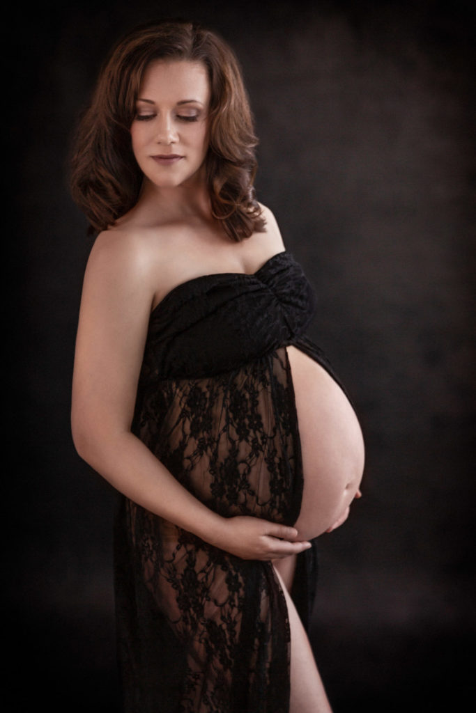 Lace maternity gown in black with slit down the front on 8 month pregnant mom standing in window light against a black background.