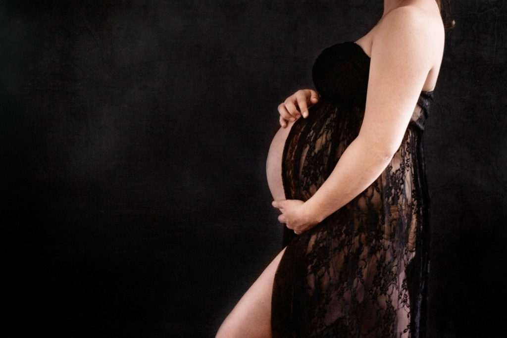 Mid Section of 8 month pregnancy in black lace maternity gown against a black background in color. Charlottesville Virginia Maternity Portraits