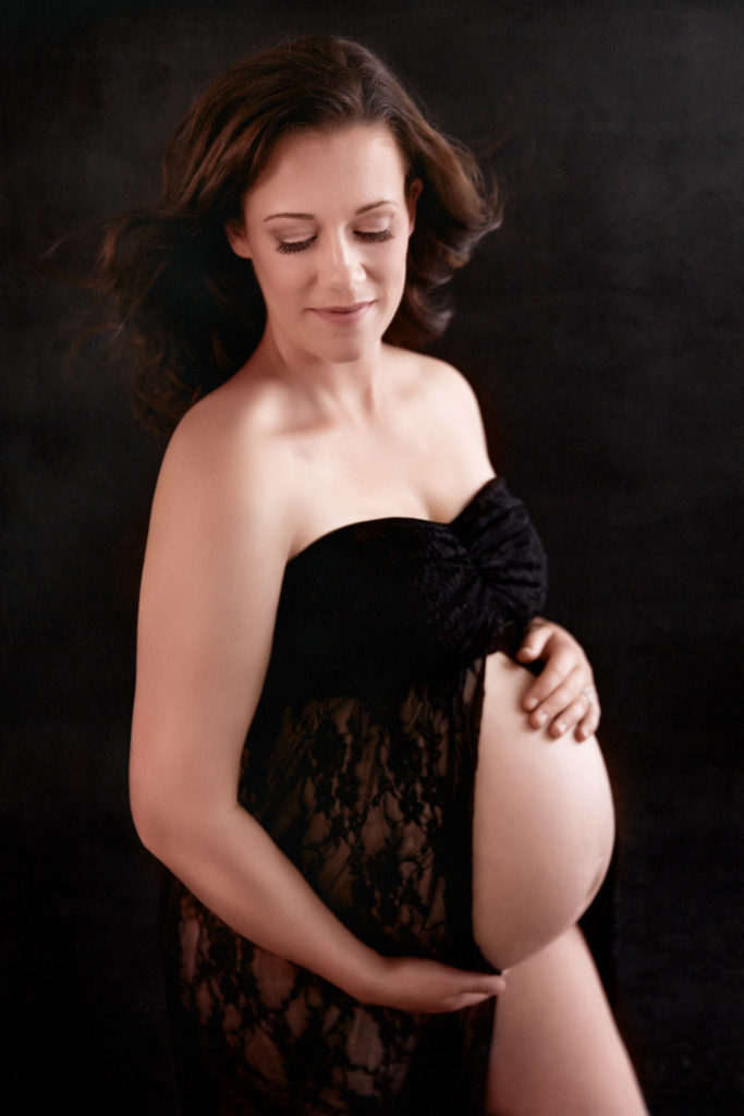 Standing maternity portrait of a mom in window light with black lace maternity gown against a black backdrop with hair blowing. Charlottesville Virginia Maternity Portraits